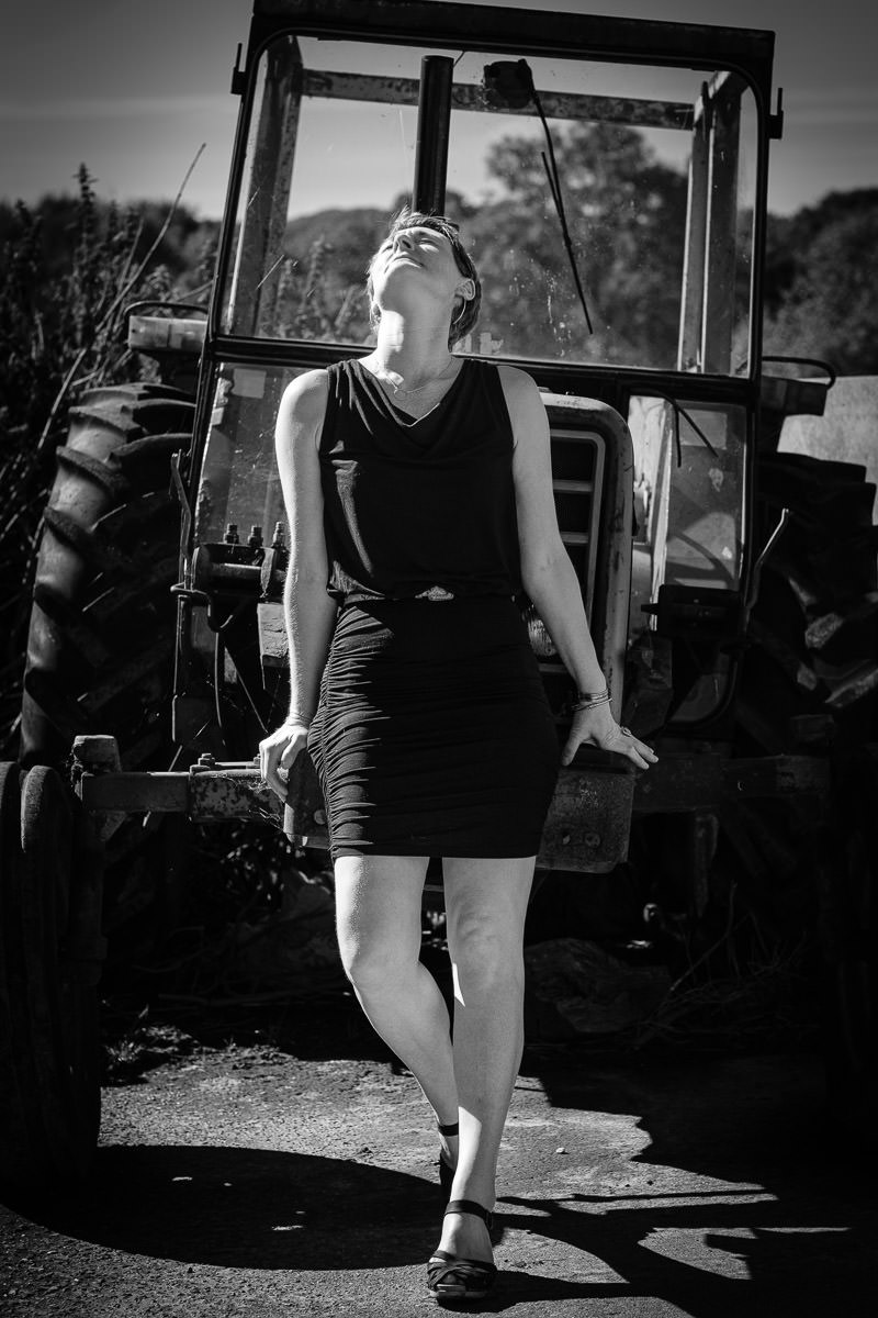woman leaning back on tractor in the sun