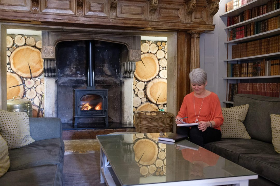 woman in orange top sitting by a big fireplace at alexander house hotel and spa