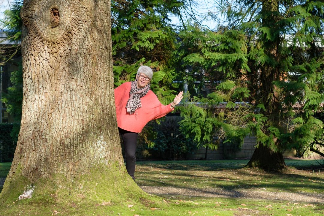 woman in orange top waving from behind a tree